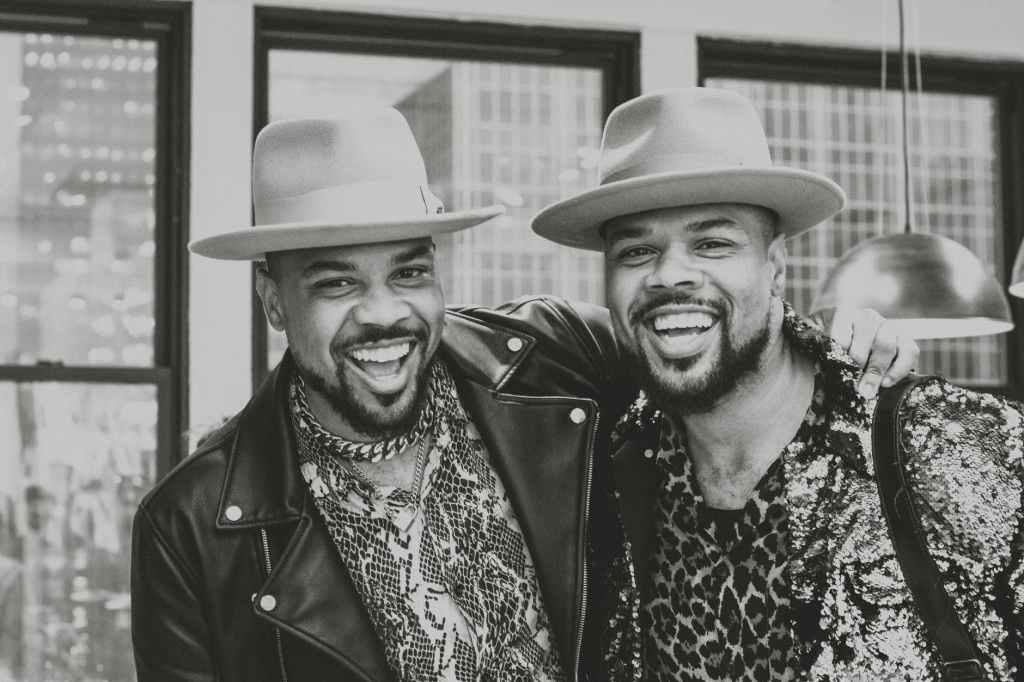 grayscale photo of male twins in same fedora hats standing together