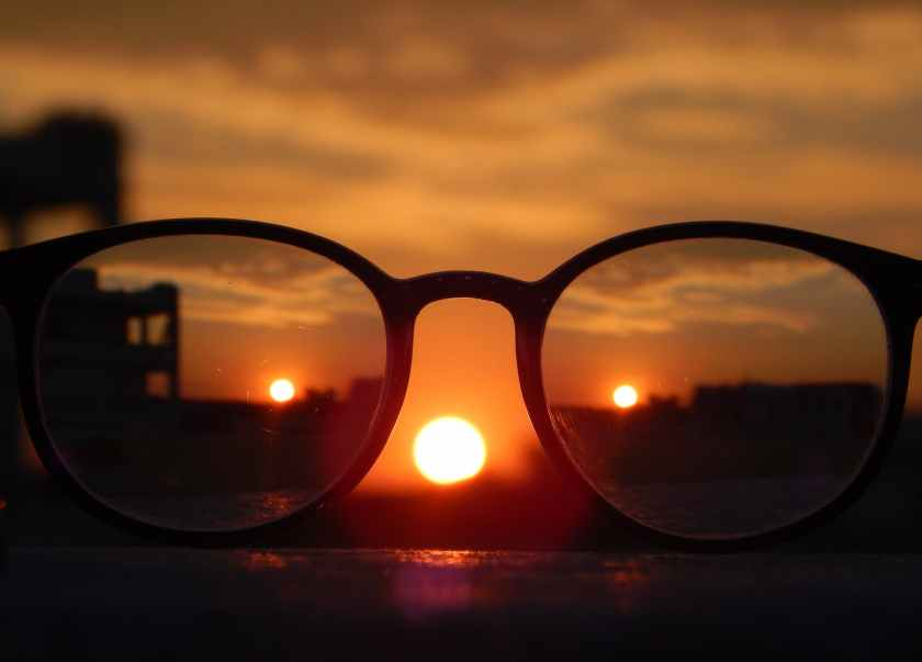 close up photography of eyeglasses at golden hour